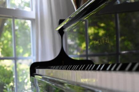 ピアノと窓と白いカーテンの写真
