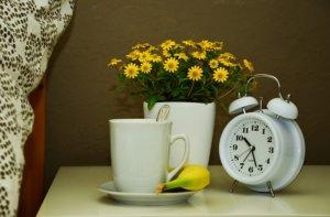 テーブルの上にコップと花と時計