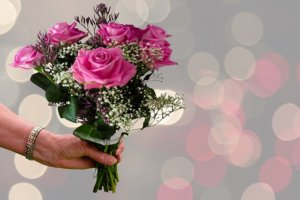 水玉の背景に手にピンクのバラ