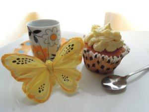 黄色い蝶とカップとケーキの写真