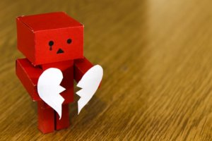 赤いロボットが破れたハートの紙を持つ