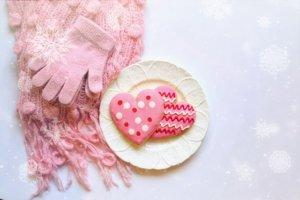 ピンクのマフラーと手袋と皿にのったクッキー