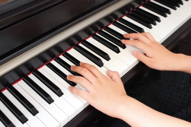 両手でピアノを弾いている